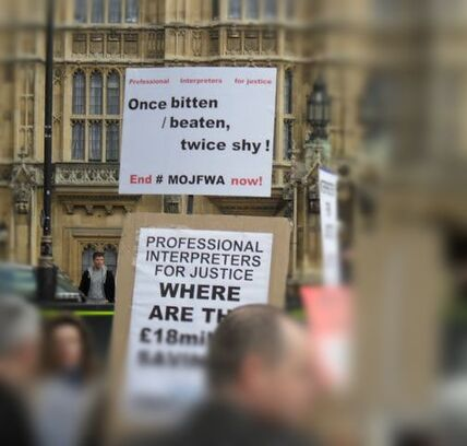 Photograph of public service interpreters demonstrating in front of Houses of Parliament with placards: Professional Interpreters for Justice, Once bitten / beaten, twice shy! End #MOJFWA now! Professional Interpreters for Justice Where are the £18 million savings! #MOJFWA
